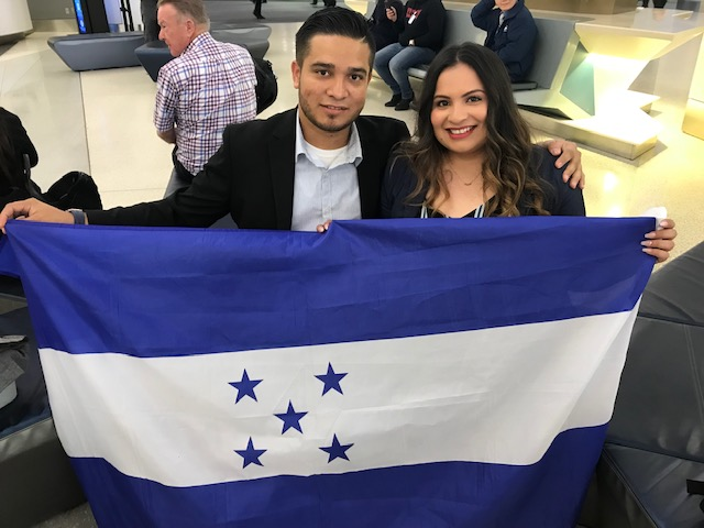 Gabriel and Soledad, narrators in Solito, Solita, unfurl the Honduran flag in support of refugees.